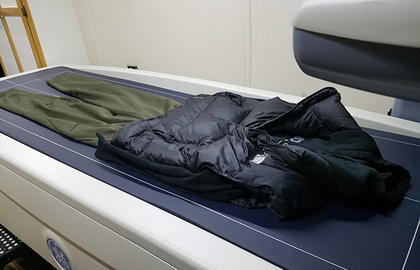 Picture of puffy vest over t-shirt and pants on the DXA scanner.